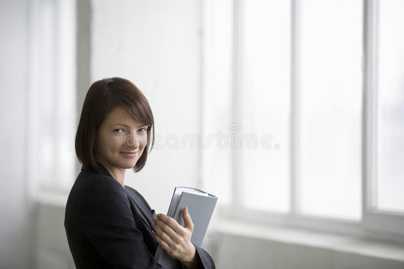 Mulher de negócios With Ring Binder Smiling In Warehouse fotos de stock royalty free