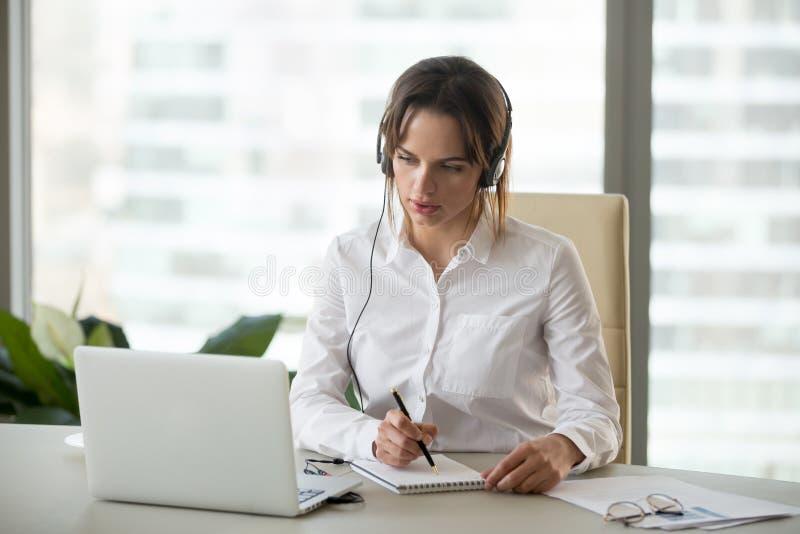 Mulher de negócios séria na observação dos fones de ouvido webinar no portátil m fotos de stock royalty free