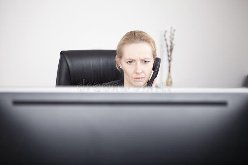 Mulher de negócios séria no telefone que olha o monitor fotografia de stock