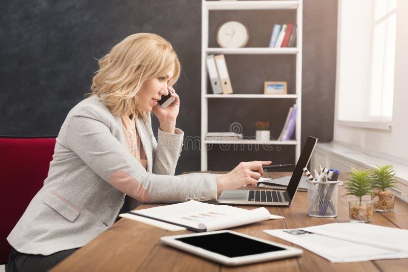 Mulher de negócios séria no trabalho que fala no telefone fotografia de stock