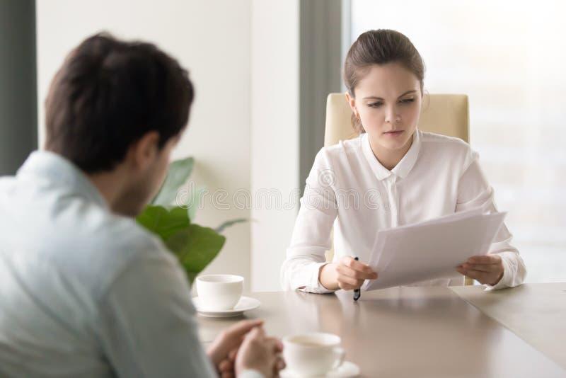 Mulher de negócios séria que estuda os papéis que sentam-se oposto ao homem em de fotografia de stock