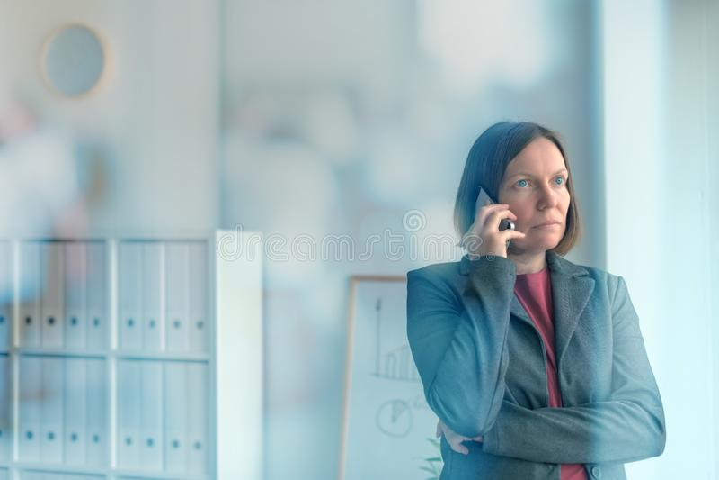Mulher de negócios séria que fala no telefone celular no escritório foto de stock