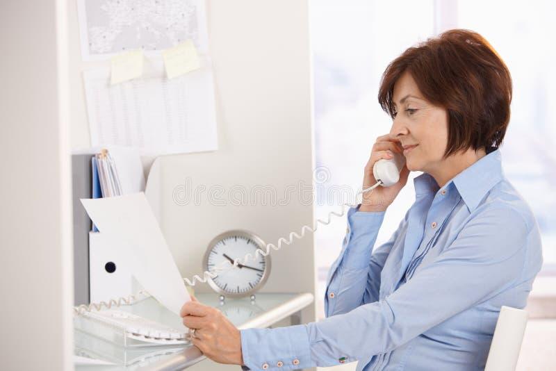 Mulher de negócios sênior no papel da leitura do atendimento de telefone. fotografia de stock