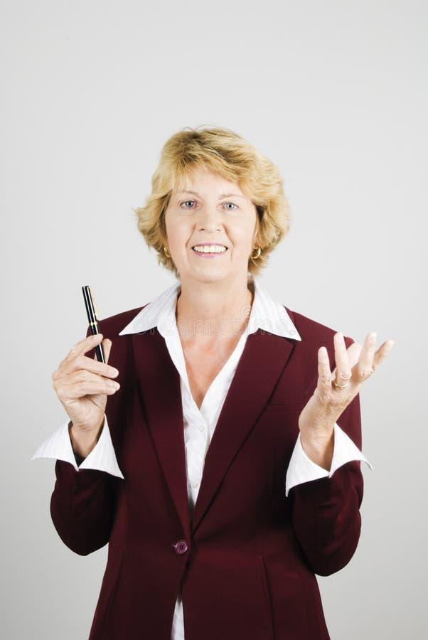 Mulher de negócios sênior que demonstra com gestu da mão imagens de stock royalty free