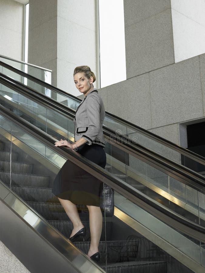Mulher de negócios segura On Escalator fotografia de stock