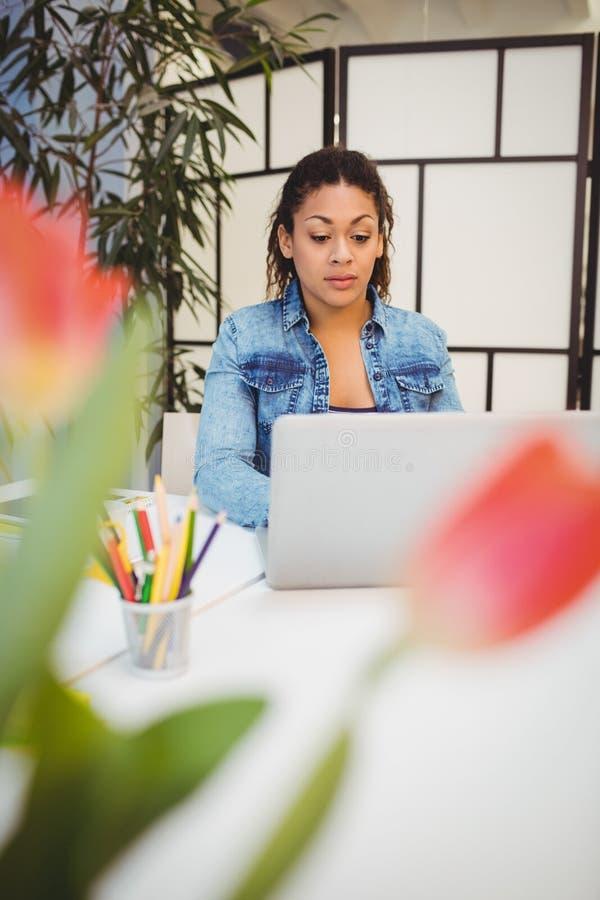 Mulher de negócios segura que trabalha no portátil na sala de reunião no escritório criativo fotografia de stock royalty free