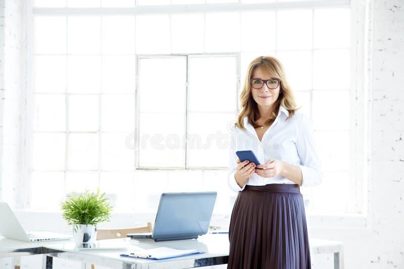 Mulher de negócios segura que usa seus telefone celular e envio de mensagem de texto ao estar no escritório fotografia de stock