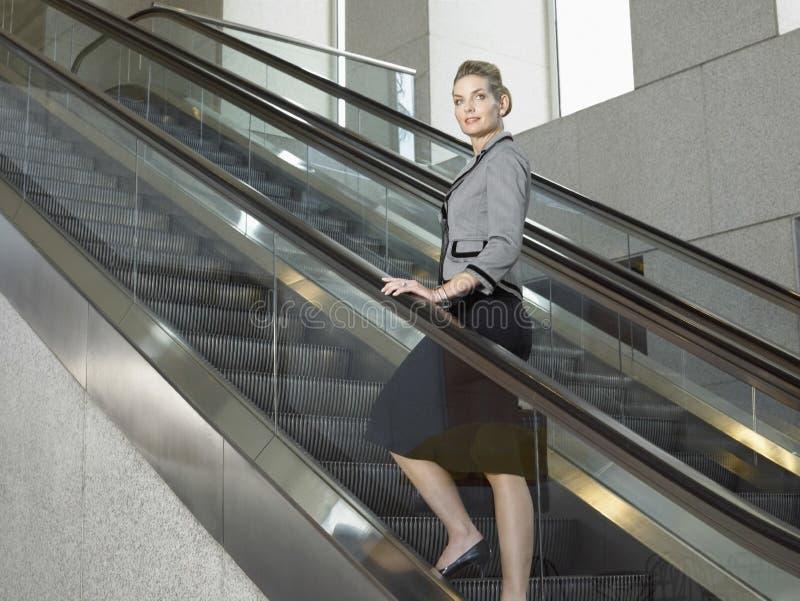 Mulher de negócios segura Standing On Escalator foto de stock