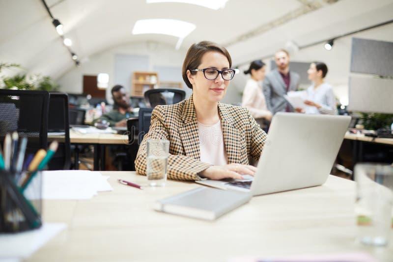 Mulher de negócios segura Working no escritório do espaço aberto foto de stock