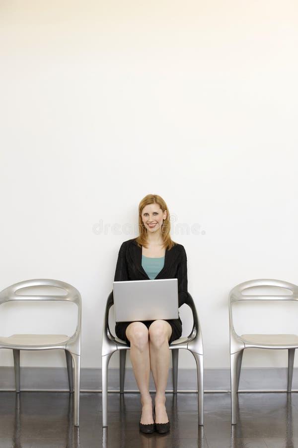 A mulher de negócios senta-se com portátil fotografia de stock royalty free