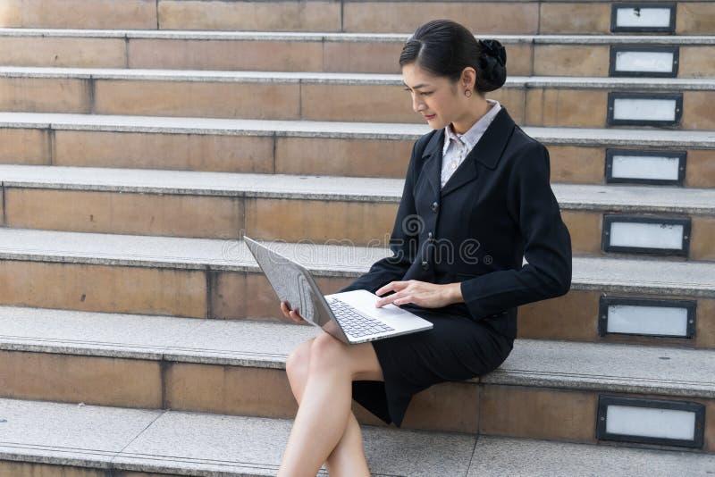 A mulher de negócios senta-se na escadaria e na palavra de datilografia no portátil foto de stock royalty free