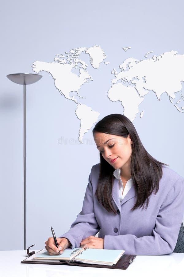 Mulher de negócios sentada em sua escrita da mesa de escritório imagens de stock royalty free