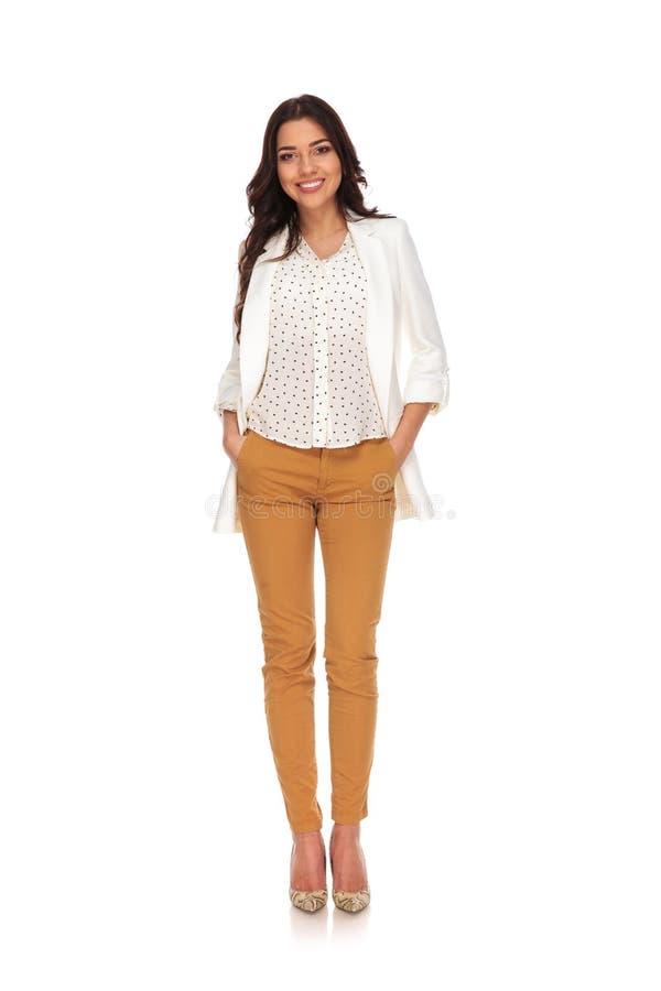 Mulher de negócios 'sexy' que está com mãos em uns bolsos ao sorrir fotos de stock
