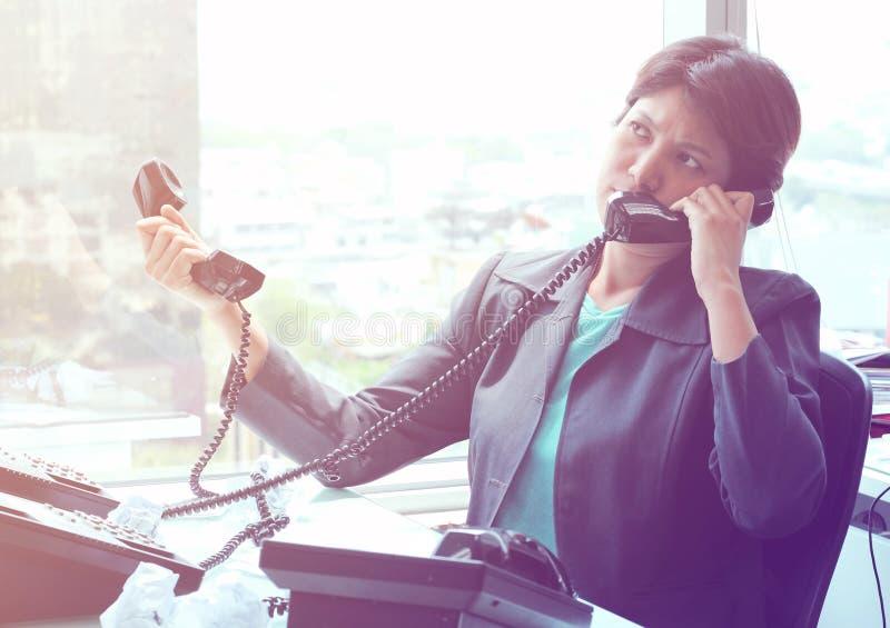 Mulher de negócios Sitting em sua mesa que responde a uma chamada telefônica fotografia de stock royalty free