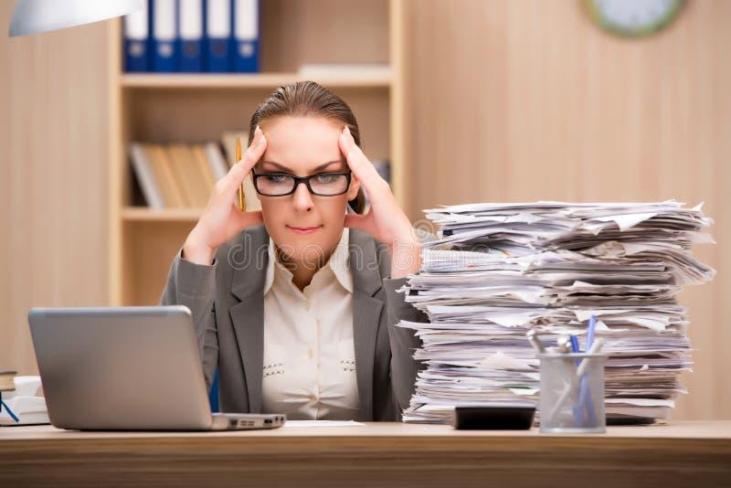 A mulher de negócios sob o esforço de demasiado trabalho no escritório fotografia de stock
