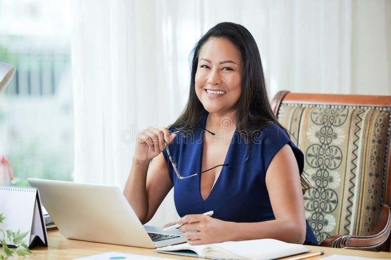 Mulher de negócios de sorriso adulta na mesa de trabalho imagem de stock royalty free