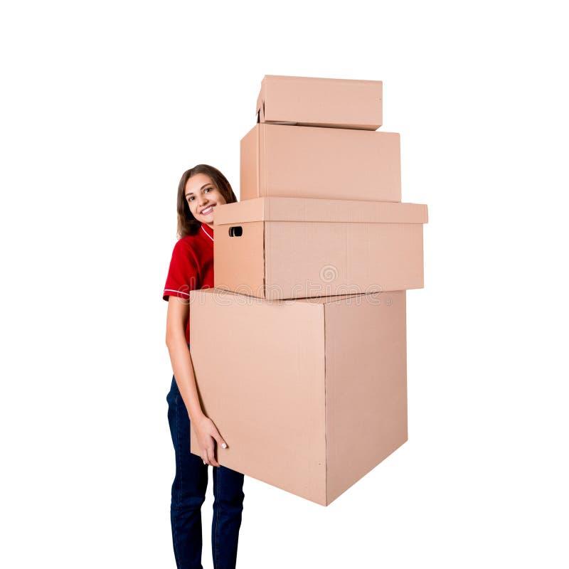A mulher de negócios de sorriso está mantendo muitas caixas de cartão grandes isoladas no fundo branco imagem de stock