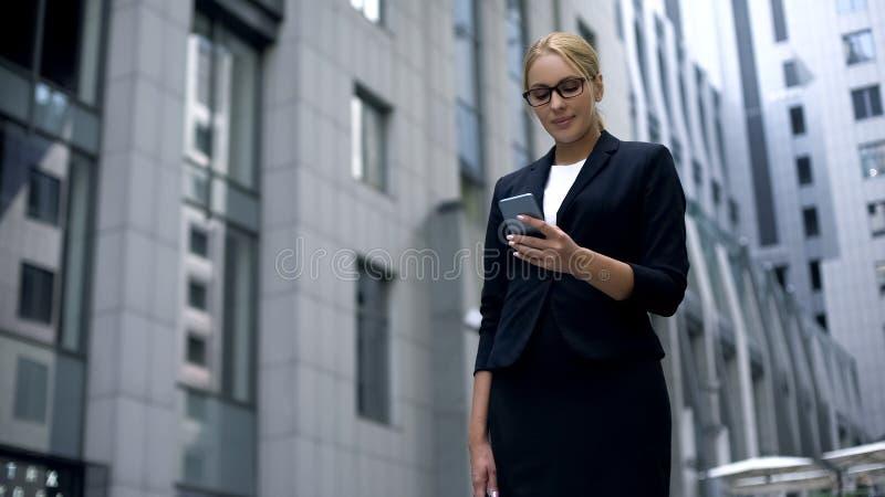 Mulher de negócios de sorriso feliz ler a mensagem no smartphone com boa notícia, salário imagens de stock