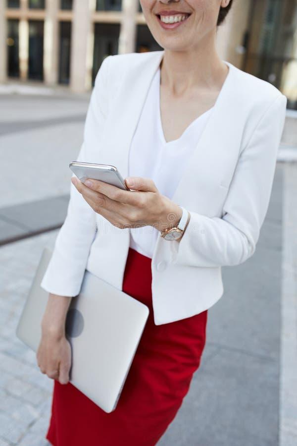 Mulher de negócios de sorriso Holding Phone foto de stock