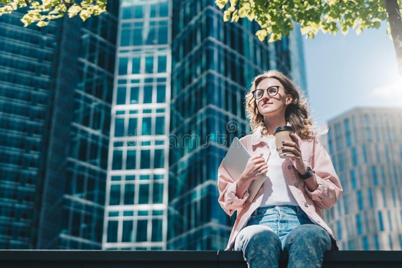 A mulher de negócios de sorriso nova do moderno nos vidros senta-se fora e guardando a tabuleta e a xícara de café digitais imagem de stock royalty free