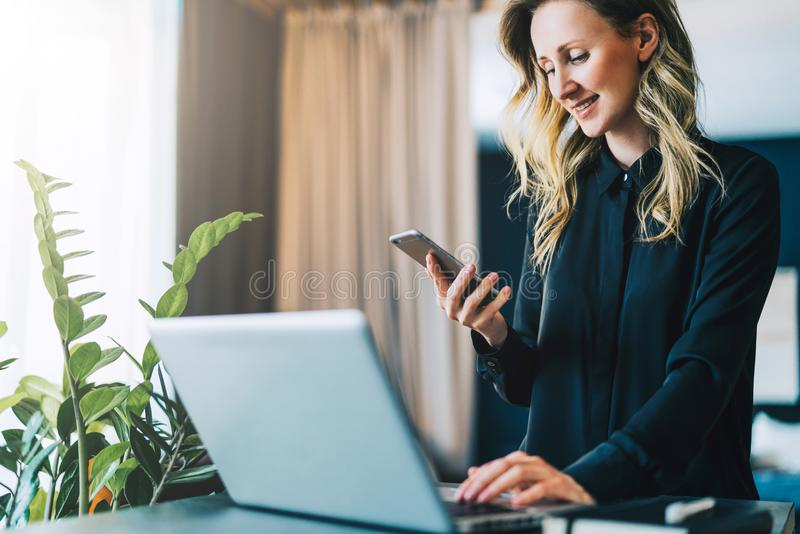 A mulher de negócios de sorriso nova na blusa está estando interna, trabalhando no computador ao usar o smartphone A menina traba imagens de stock royalty free