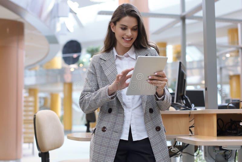 Mulher de negócios de sorriso nova no escritório que trabalha na tabuleta digital fotografia de stock royalty free