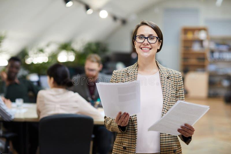 Mulher de negócios de sorriso Posing no escritório imagem de stock