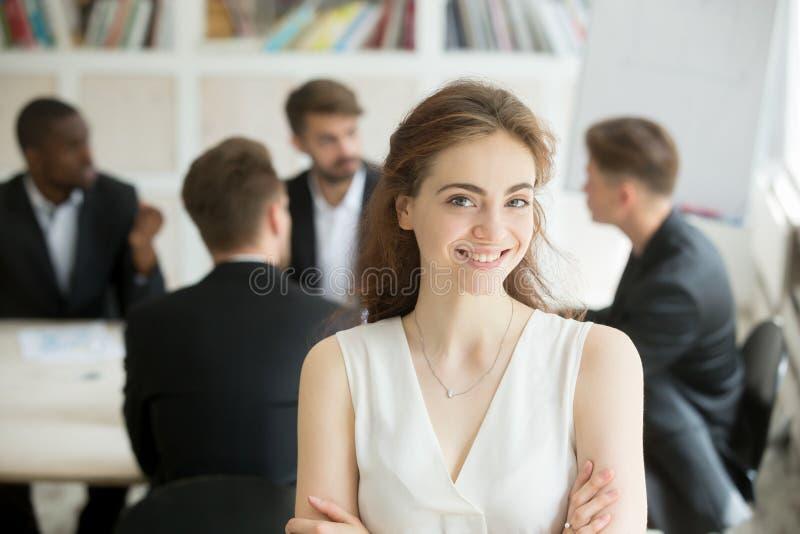 Mulher de negócios de sorriso que olha a câmera, reunião da equipe no backgro foto de stock royalty free