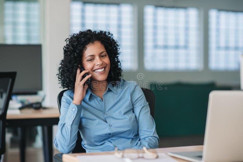 Mulher de negócios de sorriso que senta-se em sua mesa que fala em um telefone celular foto de stock