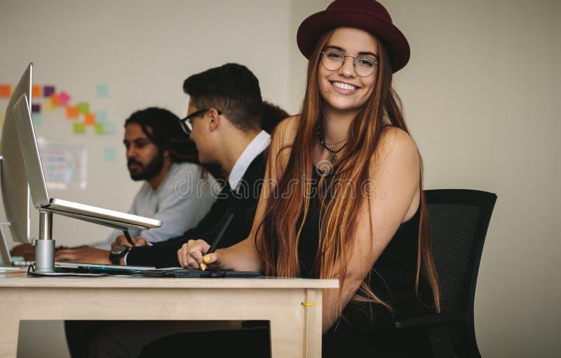 Mulher de negócios de sorriso que senta-se em sua mesa no escritório imagem de stock royalty free