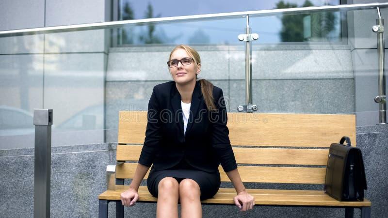 Mulher de negócios de sorriso que senta-se no banco, relaxando após o dia de trabalho fatigante fotografia de stock