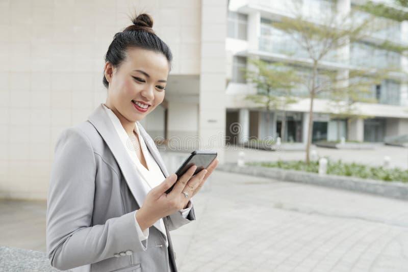 Mulher de negócios de sorriso que usa o telefone celular fora fotografia de stock