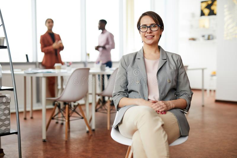 Mulher de negócios de sorriso Sitting na cadeira imagem de stock royalty free