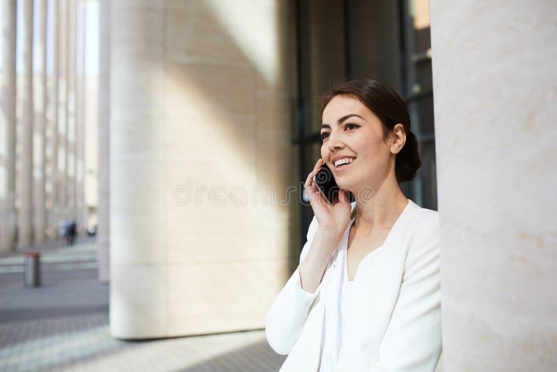 Mulher de negócios de sorriso Speaking pelo telefone imagens de stock
