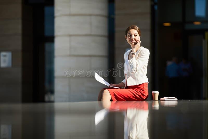 Mulher de negócios de sorriso Speaking pelo telefone na luz solar fotografia de stock royalty free