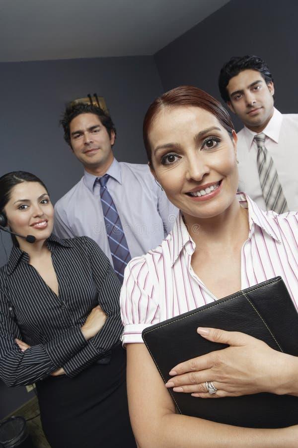 Mulher de negócios Standing With Colleagues no escritório imagem de stock