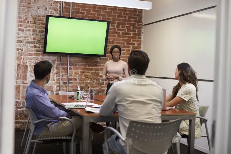 Mulher de negócios Standing By Screen para entregar a apresentação fotografia de stock royalty free