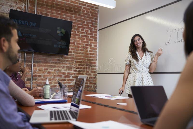Mulher de negócios Standing By Whiteboard para entregar a apresentação foto de stock