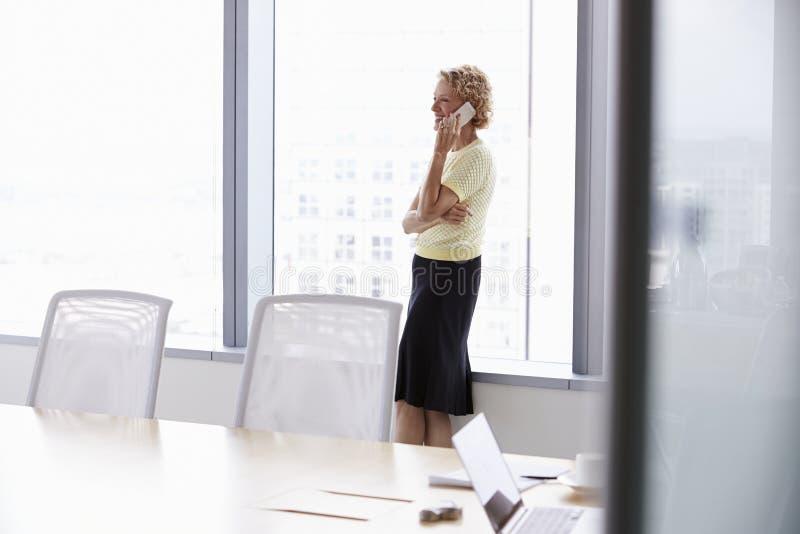 Mulher de negócios superior On Mobile Phone na sala de reuniões fotografia de stock