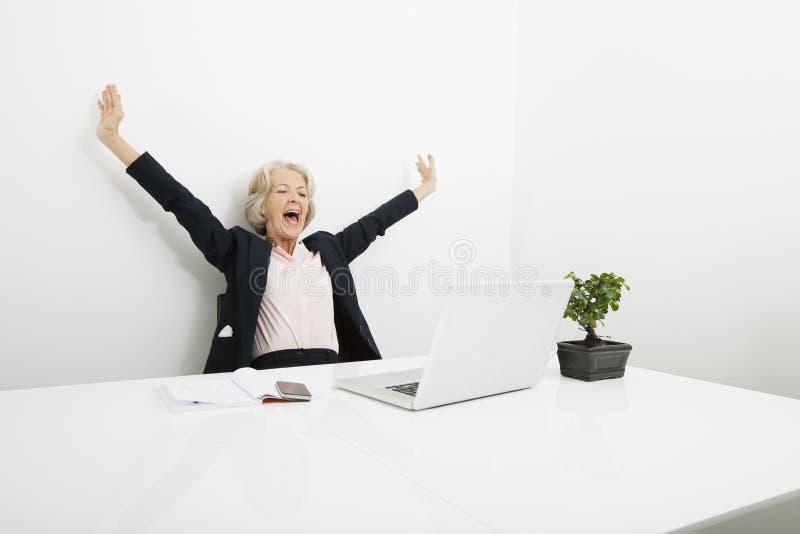 Mulher de negócios superior que boceja ao olhar o portátil no escritório imagens de stock royalty free
