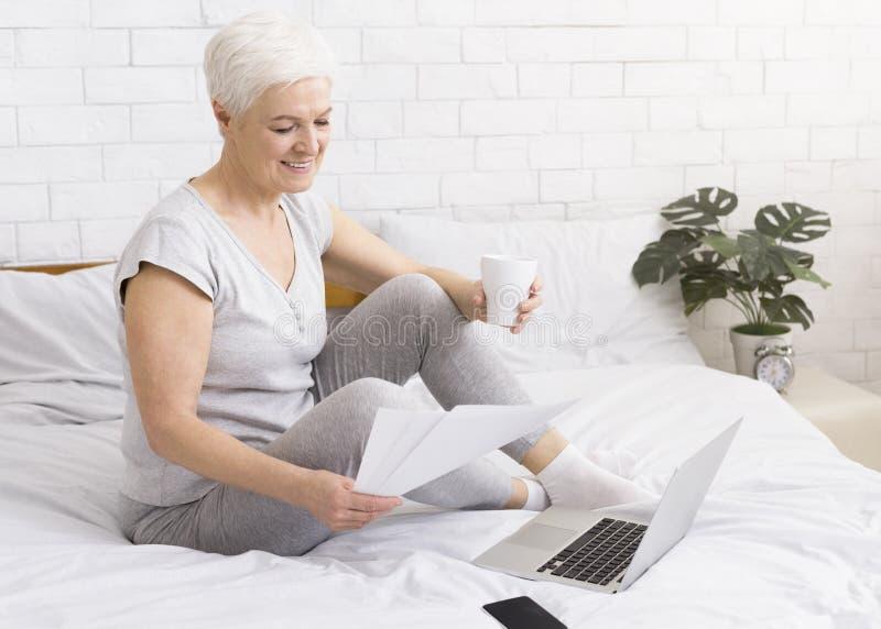 Mulher de negócios superior que trabalha com documentos e portátil fotografia de stock