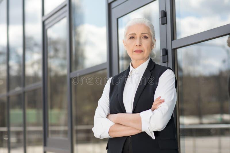 Mulher de negócios superior segura bonita que está com braços cruzados e que olha a câmera imagem de stock royalty free
