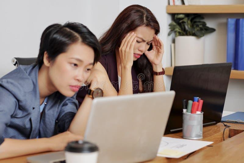 A mulher de negócios tem uma dor de cabeça durante o dia do trabalho foto de stock