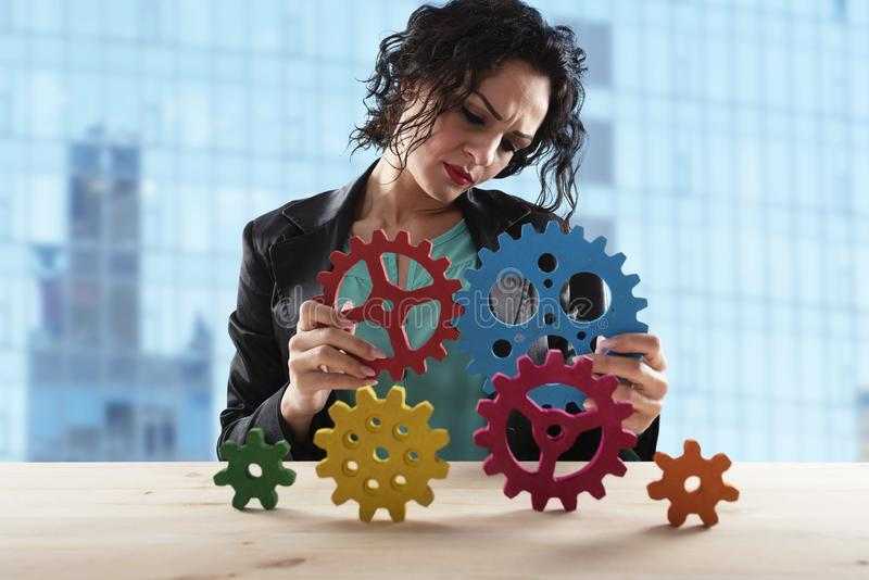 A mulher de negócios tenta conectar partes das engrenagens Conceito dos trabalhos de equipe, da parceria e da integração imagens de stock