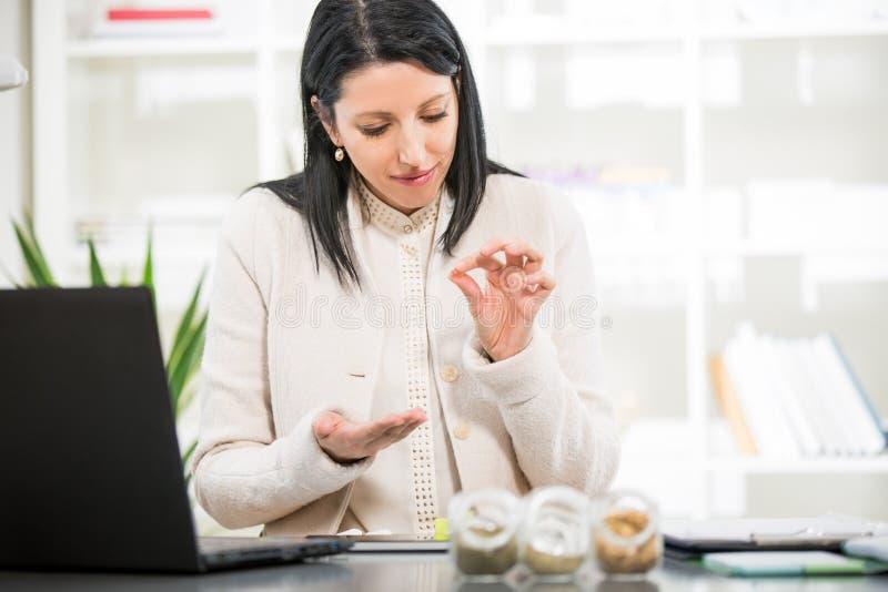 A mulher de negócios toma comprimidos homeopaticamente imagens de stock