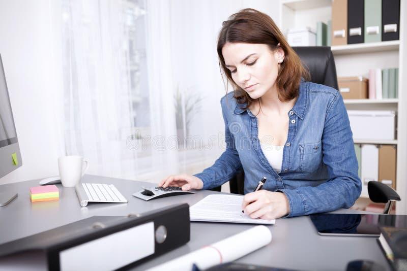 Mulher de negócios trabalhadora que senta-se escrevendo um relatório foto de stock royalty free