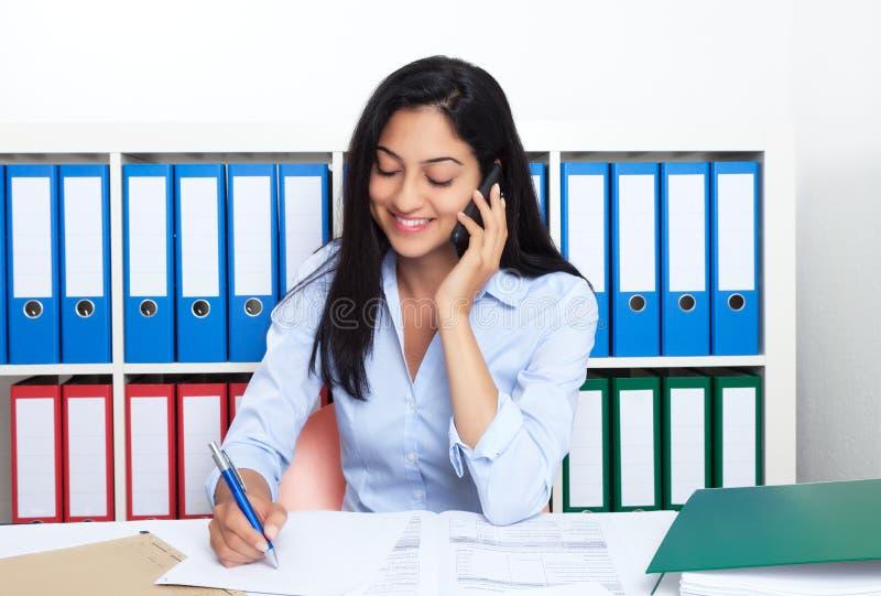 Mulher de negócios turca faladora com o telefone no escritório foto de stock royalty free