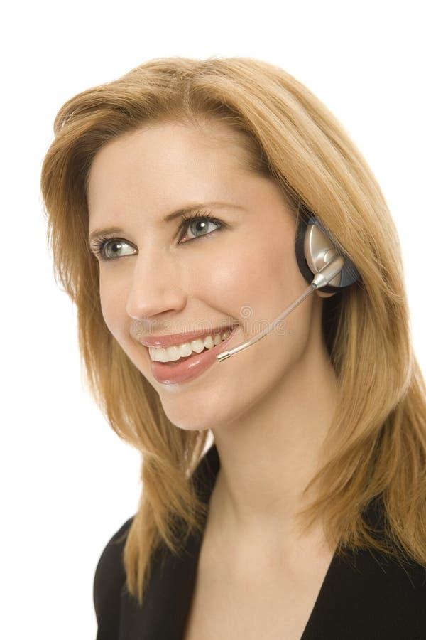 A mulher de negócios usa auriculares fotografia de stock royalty free