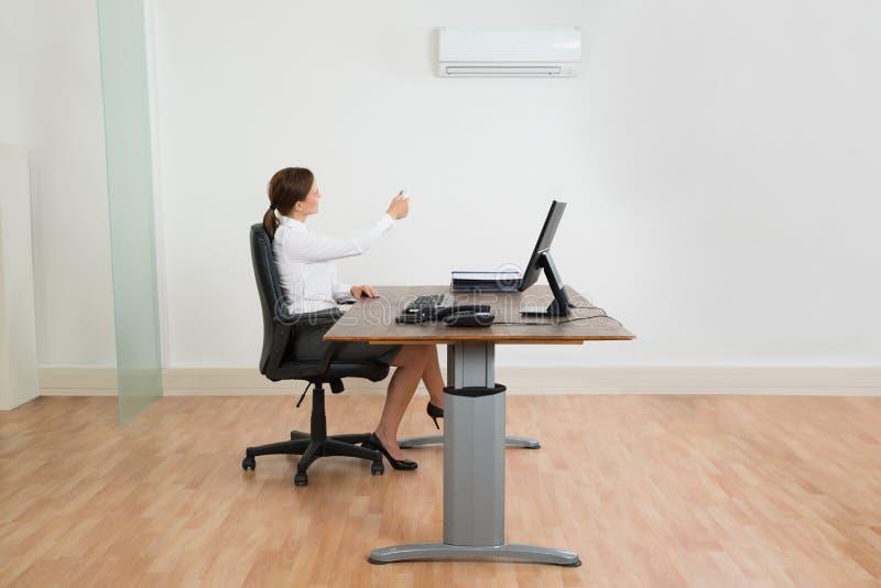 Mulher de negócios Using Air Conditioner no escritório imagens de stock