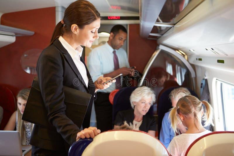 Mulher de negócios Using Mobile Phone no trem da periferia ocupado imagens de stock